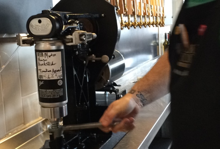 A bartender at Whole Foods Park Lane seals a crowler. It takes less than 20 seconds.