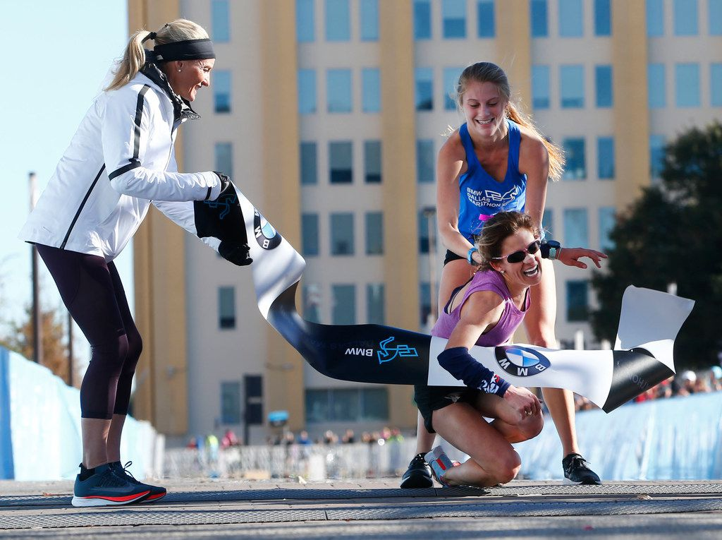 Shalane Flanagan, four-time Olympian, left, watches as Chandler Self, winner of the full marathon, is helped by relay runner Ariana Luterman, 17, from Greenhill School, at the finish line during the BMW Dallas Marathon in downtown Dallas, Sunday, Dec. 10, 2017.  (Nathan Hunsinger/The Dallas Morning News)