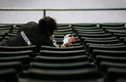 Mirella Santoyo cleans trash from audience seating areas at Reunion Arena after the Plano Senior High graduation on June 10, 2008.