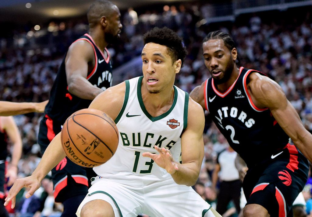 Milwaukee Bucks guard Malcolm Brogdon (13) receives a pass as Toronto Raptors forward Kawhi Leonard (2) looks on during the first half in Game 1 of the NBA basketball playoffs Eastern Conference final in Milwaukee on Wednesday, May 15, 2019. (Frank Gunn/The Canadian Press via AP)