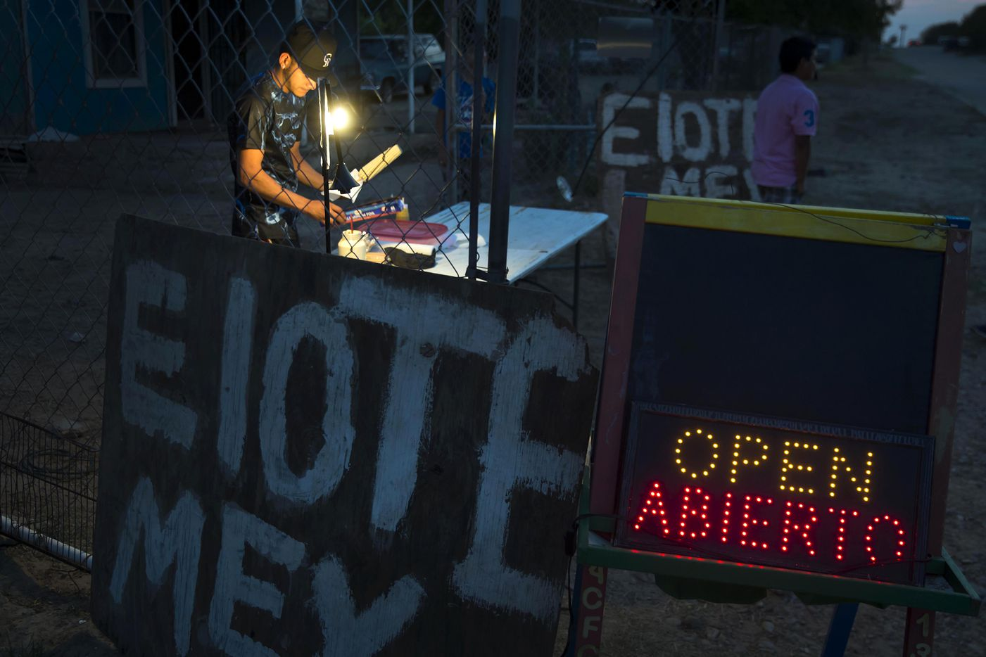 Cesar Rivera sells Elotes (grilled Mexican street corn) outside his grandmother's home in El Cenizo, Texas.