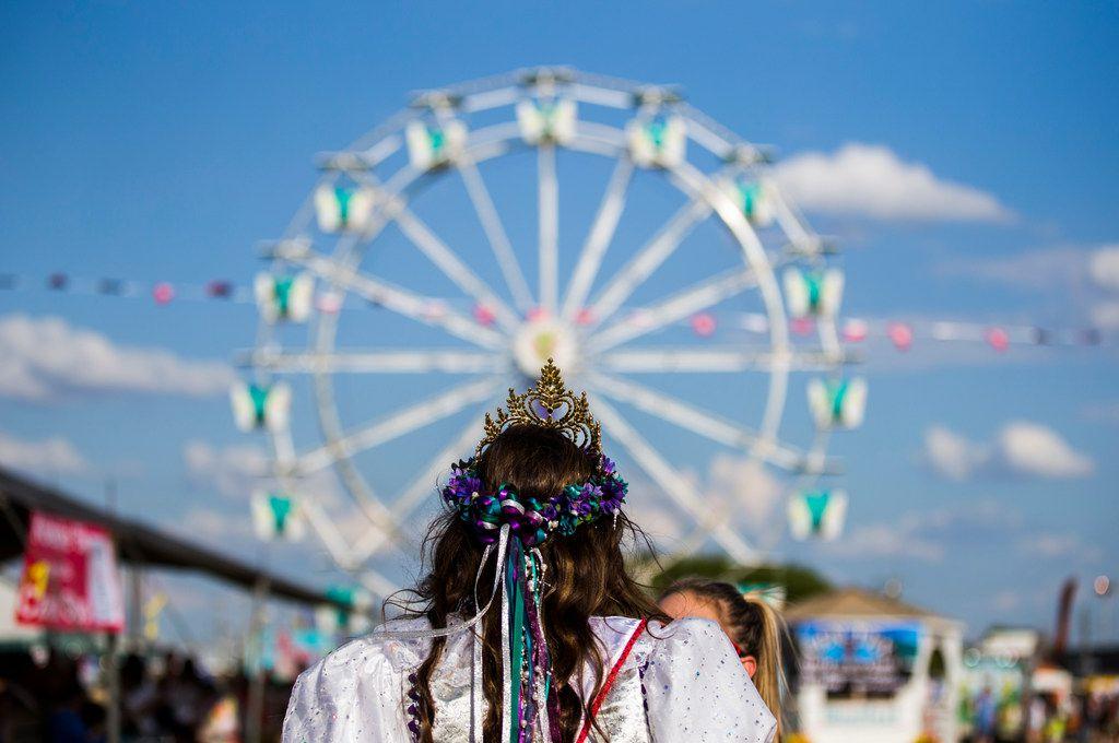 Miss West Fest 2018 Abby Kolar, 18, walks toward a Ferris wheel on the Westfest grounds.