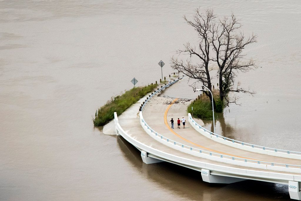 Floodwaters from the swollen Trinity River surround a roadway as people walk from the Sylvan Avenue bridge toward the flooded Trinity River Greenbelt Park on May 29, 2015, in Dallas. (Smiley N. Pool/The Dallas Morning News)