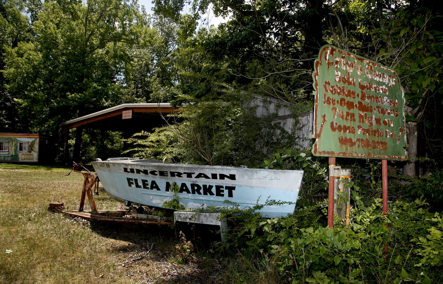 A faded sign advertising Crip's Camp stands beside an old boat advertising a flea market across the road in Uncertain, Texas Tuesday June 26, 2018.