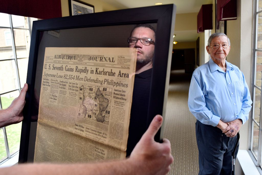 Will Williford, director of sales and marketing, left, is seen in the reflection of a glass frame, and Air Force veteran Jorge Masek, 87, at the Treemont Retirement Community in North Dallas. The newspaper clipping Williford is holding is one of four clippings that is framed and on display at the center honoring the veteran residents.