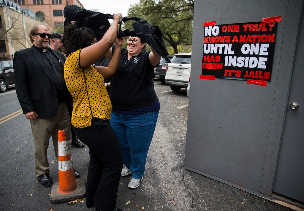 Legislative Aid Jennifer Russell of Houston (center) puts on a protective vest like those used by correctional officers before stepping in to  a heated, mock prison cell outside the state capitol on Tuesday, March 12, 2019 in Austin. Correctional Officer Elizabeth Dean (right), who works in the Holliday Unit in Huntsville, Texas, helps Russell put on the vest. Texas Prisons Air-Conditioning Advocates set up the cell, and challenged people to spend three minutes inside.