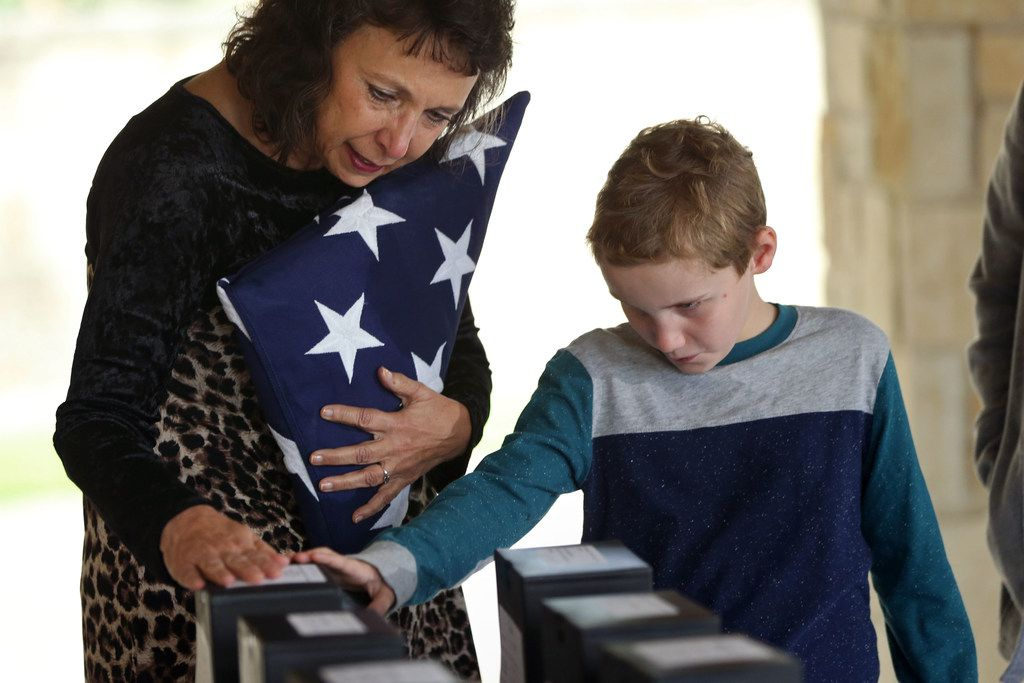 Suzy Robinson and her grandson Hayden Robinson touch the box containing the remains of her husband, U.S. Army veteran Jerry Robinson, at the Dallas-Fort Worth National Cemetery.