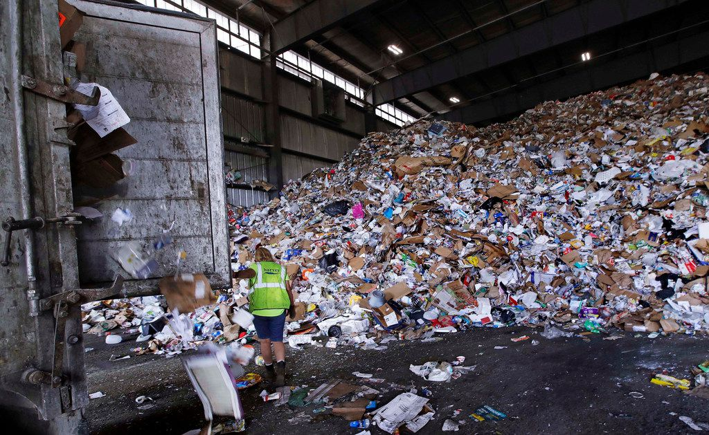 A trailer door is opened on a truck filled with unsorted recyclable trash as it is offloaded and added to a giant pile in a processing building in Westborough, Mass. Recycling programs across the United States are shutting down or scaling back because of a global market crisis blamed on contamination at the curbside bin.
