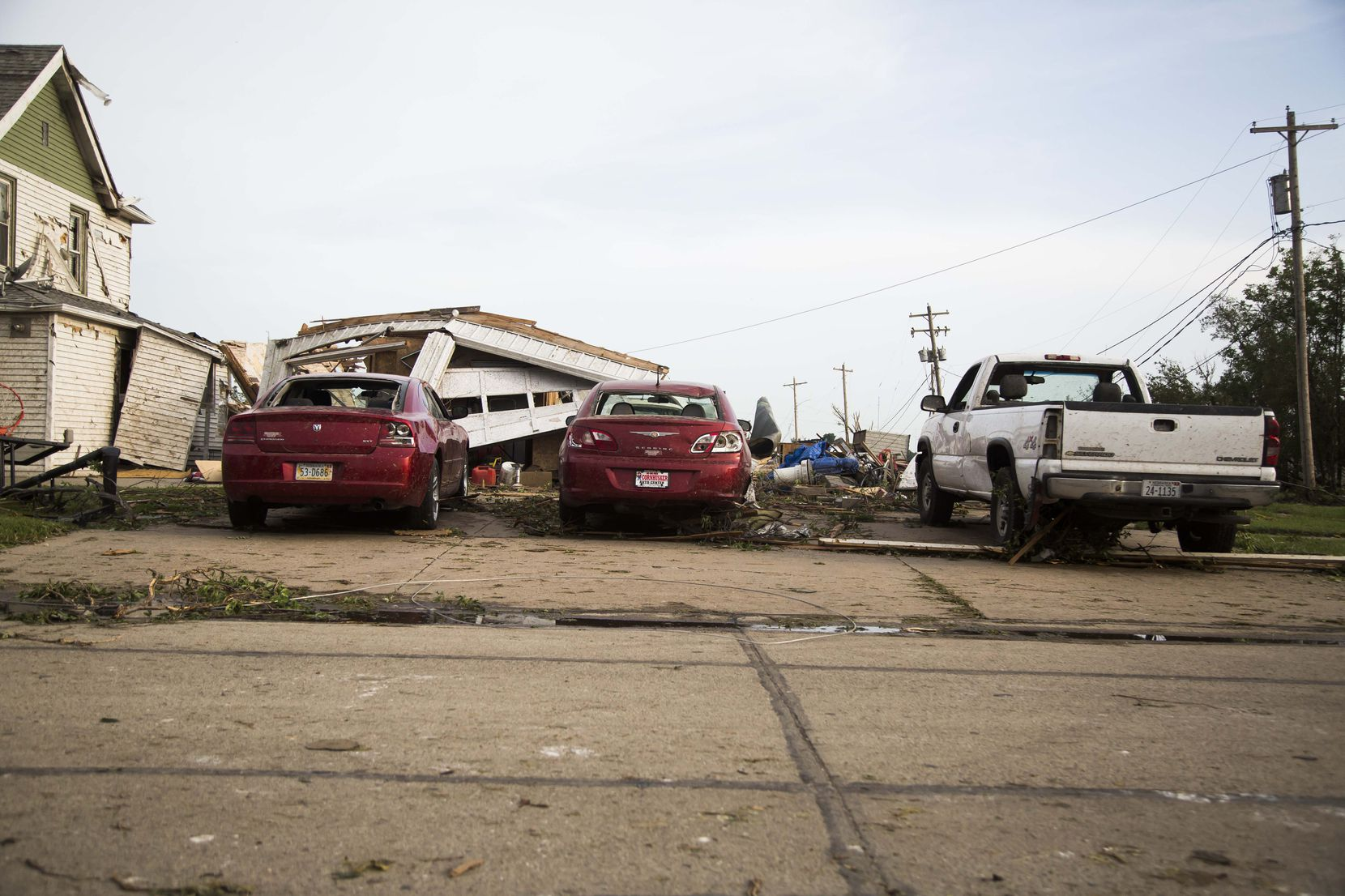 Damaged cars are parked in front of a garage that was torn down by a tornado on Monday, June 16, 2014, in Pilger, Neb. The National Weather Service said at least two twisters touched down within roughly a mile of each other. (AP Photo/The Journal-Star, Stacie Scott)