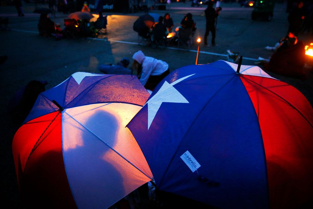 People take cover from the light rain under Texas flag umbrellas.  they were waiting for it to get dark enough to  light paper lanterns and release them into the night sky during the Lantern Festival at Texas Motorplex in Ennis, Texas, Saturday, March 4, 2017. (Tom Fox/The Dallas Morning News)