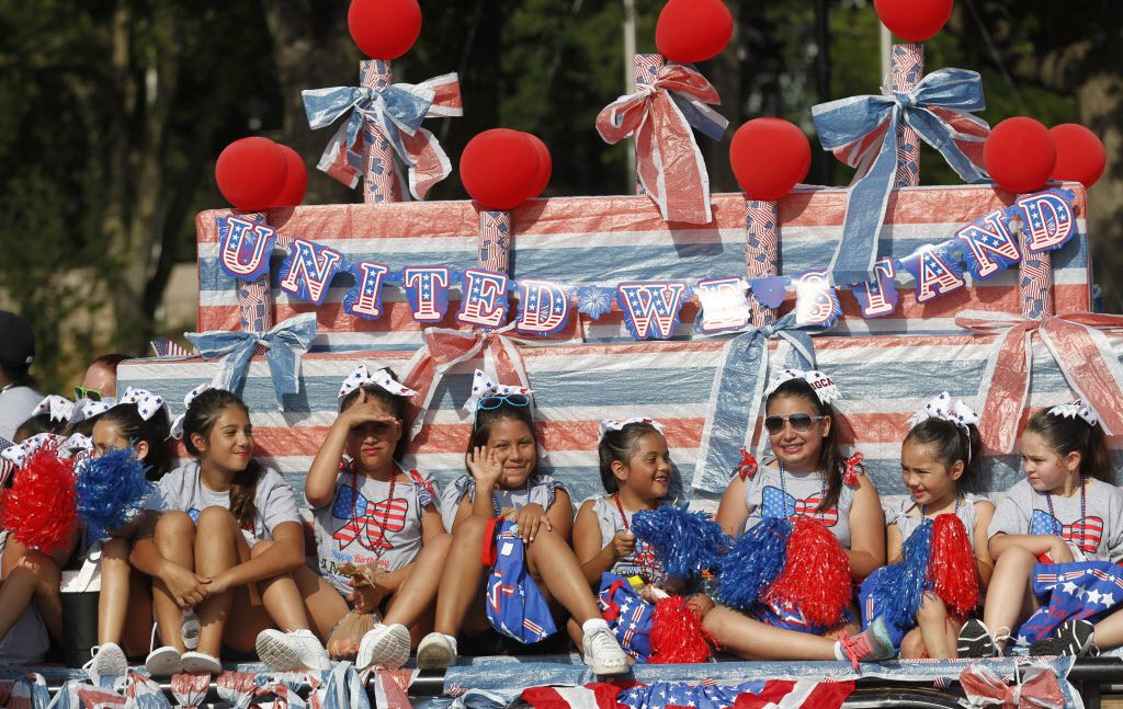 Members of the Irving Girls Cheerleading Association ride a float during the Irving 4th of July parade in Irving, Texas on Saturday, July 4, 2015.