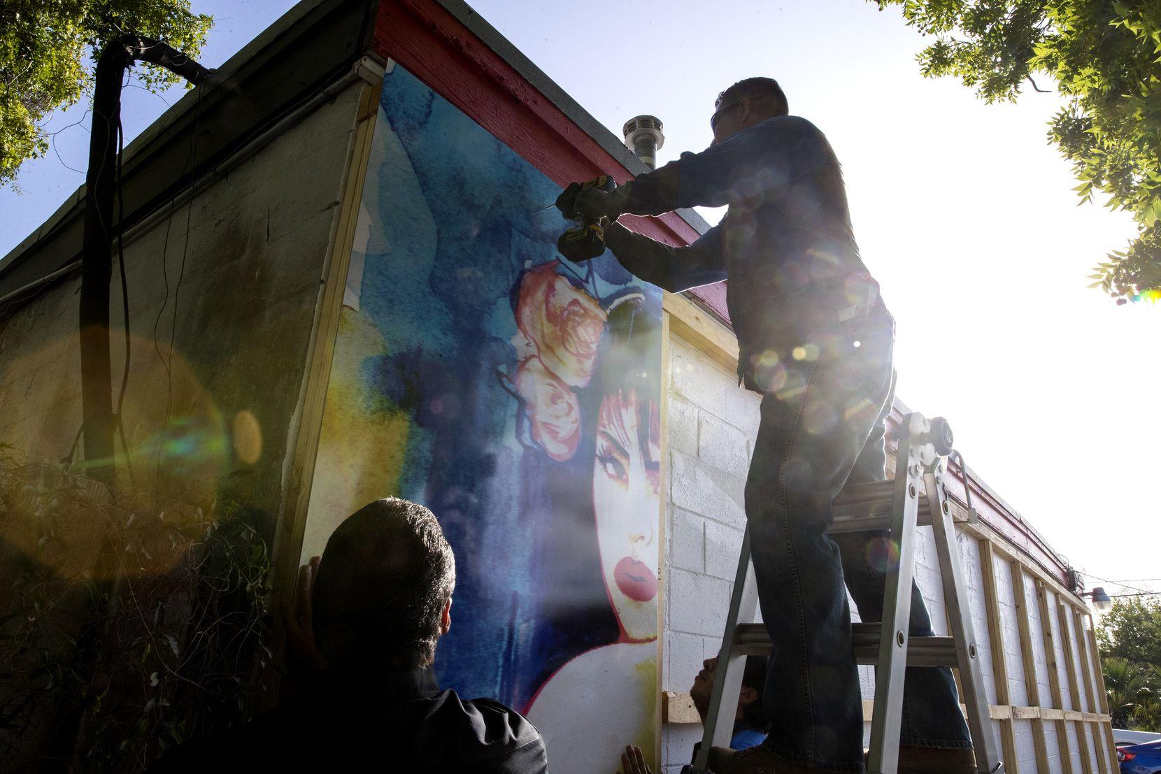 Trabajadores instalan un nuevo mural de Selena afuera de una tienda de comida en Molina, barrio de Corpus Christi.