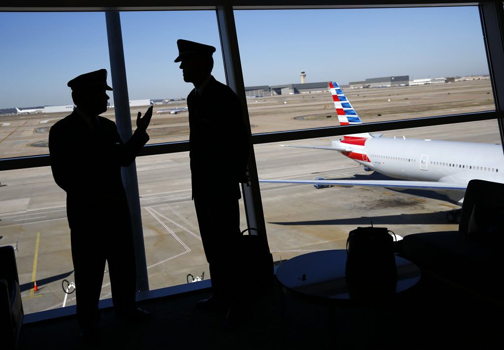 US Airways pilots visit before the newly painted American Airlines 777 following the press conference announcing the merger of US Airways and American Airlines  at Dallas Fort Worth International Airport..  (Tom Fox/The Dallas Morning News) 08202013xNEWS