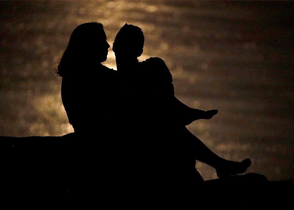 Silueta de una pareja que conversa bajo la luz de la luna en la ribera del río Missouri en Kansas City el 27 de junio del 2018. Ambientes como este pueden ser propicios para hablar de las finanzas de una pareja, charlas que son vitales para la salud de la relación, según expertos.