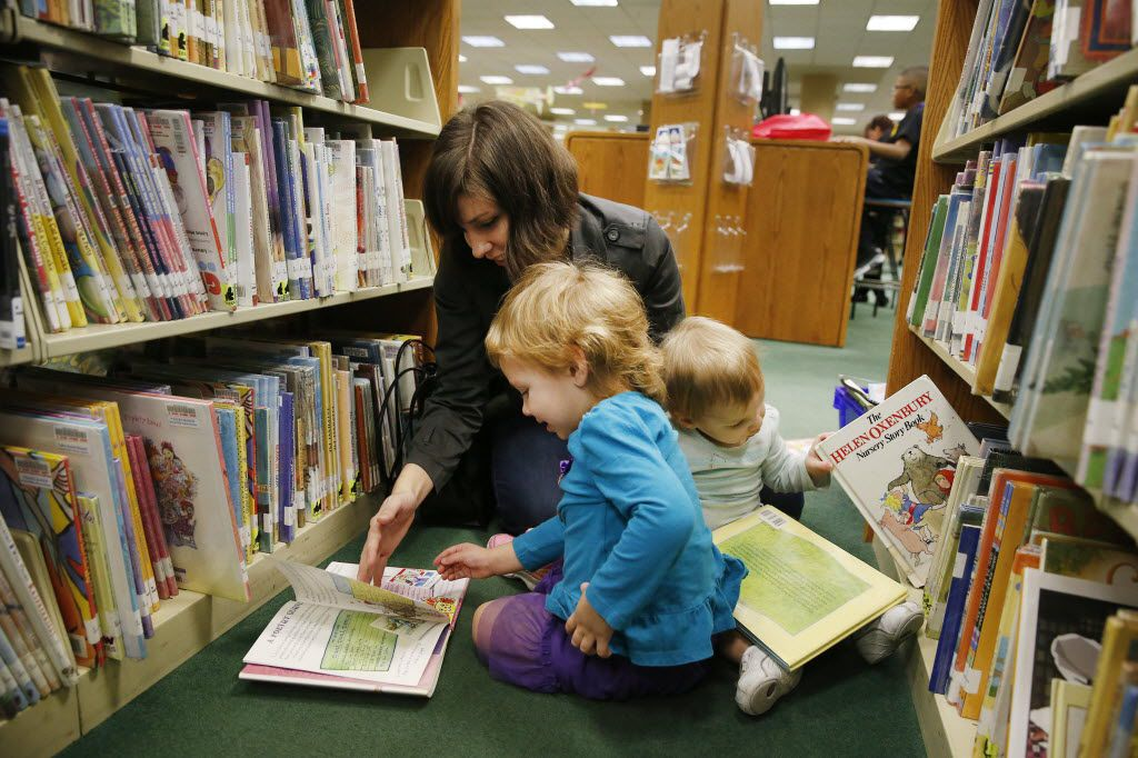 Melodi Smith (top left), of Irving, Texas, reads a book with her daughter, Violet Smith (bottom left), 3, while her other daughter, Lillian Smith, 18 months old, looks through books in the children's section inside the Irving Central Library in Irving Saturday January 31, 2015.