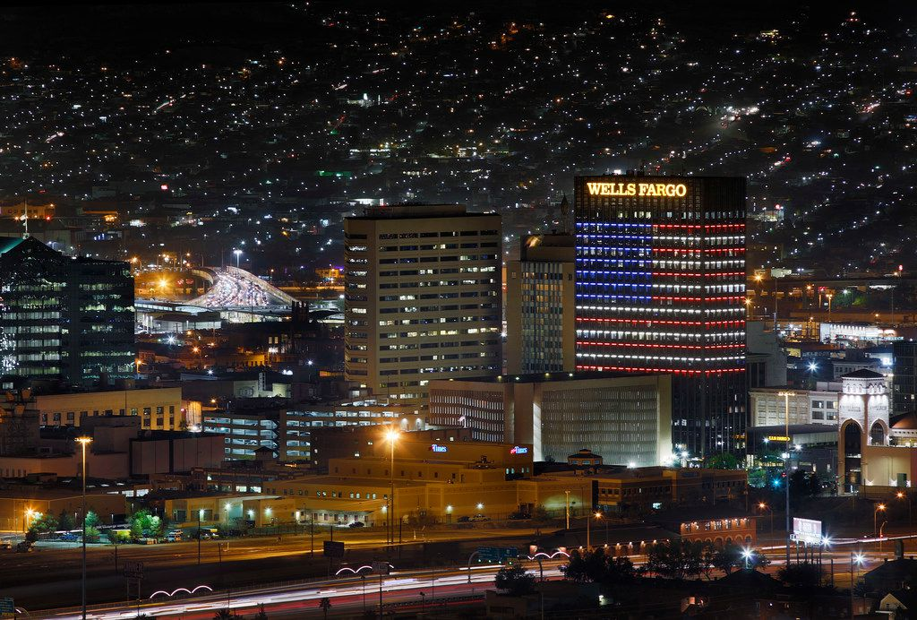 The Wells Fargo building in downtown El Paso, Texas is lit with a U.S. flag as traffic entering the United States crosses over the Paso Del Norte Bridge (left) from neighboring Ciudad Juarez, Mexico, Thursday, November 8, 2018.