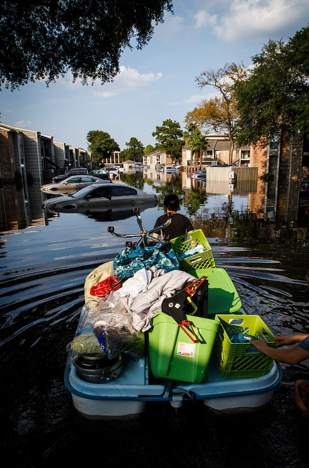 Jeff Liu is helped by his mother Rhoda as they float his belongings from his west Houston apartment through flood waters from Hurricane Harvey using a paddle boat on Saturday, Sept. 2, 2017, in Houston.