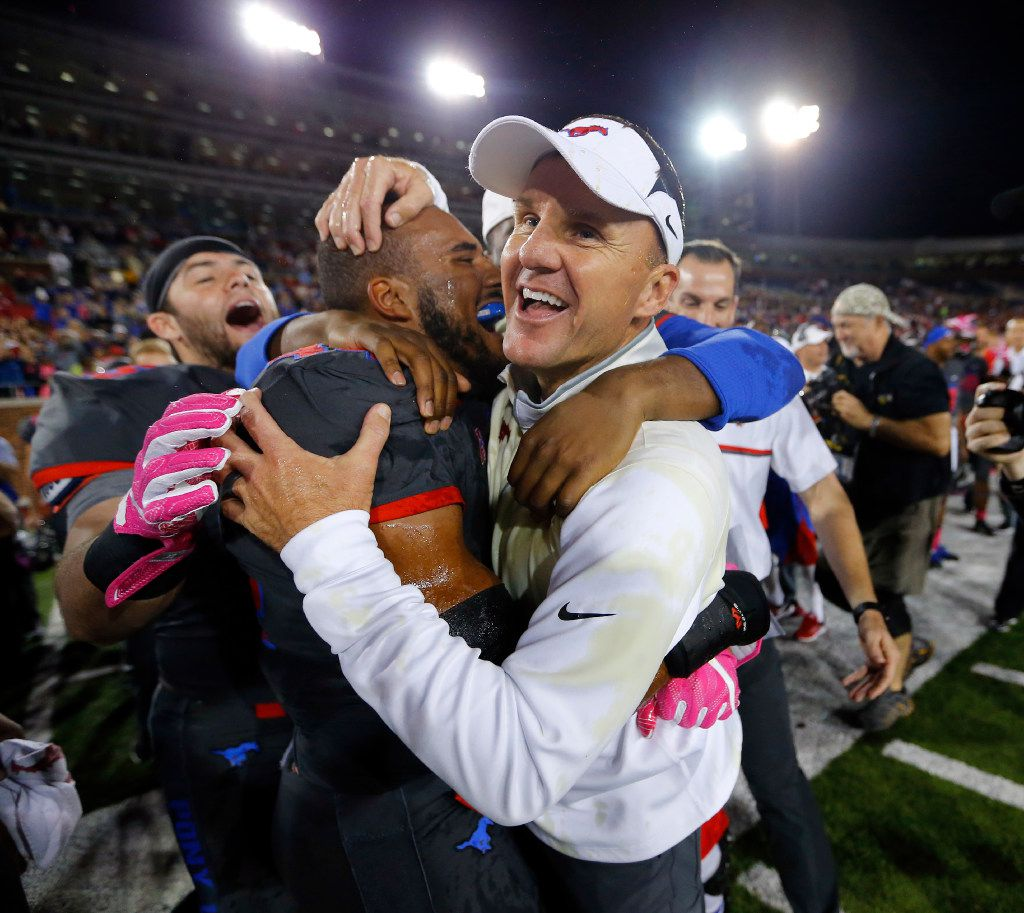 Southern Methodist Mustangs head coach Chad Morris is congratulated by linebacker Jackson Mitchell (44) after their upset win over the Houston Cougars at Gerald J. Ford Stadium in University Park, Texas, Saturday, October 22, 2016. SMU upset Houston, 38-16.  (Tom Fox/The Dallas Morning News)