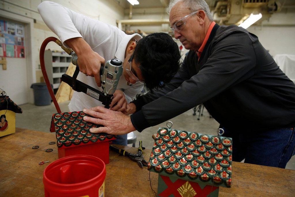 Sophomore Servando Badillo works with shop teacher Doug Palmer to affix bottle caps for the roof of his birdhouse during shop class at Skyline High School.
