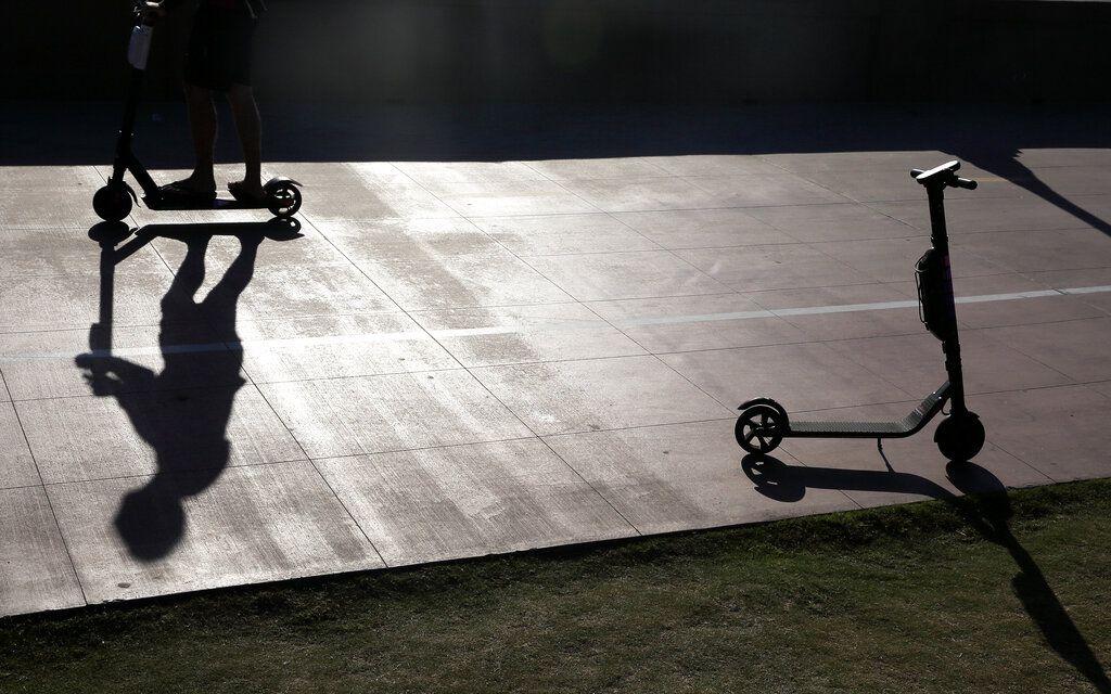 ARCHIVO – En esta foto de archivo del 28 de mayo de 2019, un hombre en patinete pasa junto a un patinete estacionado en la rambla de Mission Beach, San Diego, EEUU. A medida que se populariza el uso del patinete en un centenar de ciudades alrededor del mundo, sus usuarios están expuestos a juicios por daños y probablemente no tienen seguro contra accidentes. (AP Foto/Gregory Bull, File)