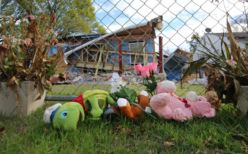 The memorial to Linda Rogers at 3534 Espanola Drive in northwest  Dallas is seen in front of a security fence, as the house which exploded because of a gas leak sits in disrepair in the background, photographed on Wednesday, March 21, 2018.