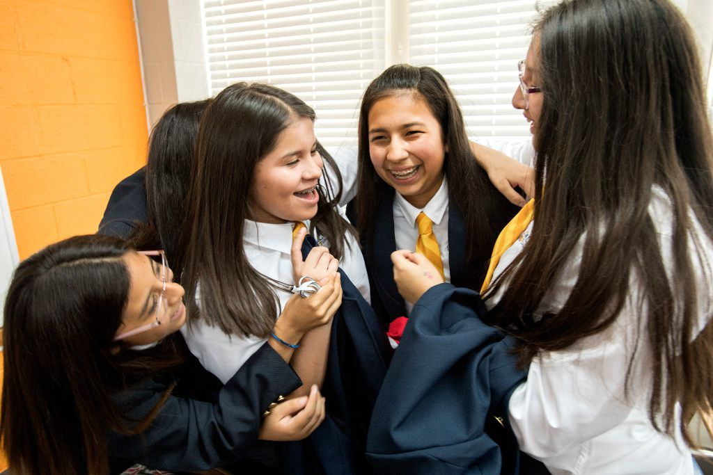 Left to right: Cristo Rey Dallas College Prep incoming freshmen Guadalupe Favela, 13, Samira Sifuentes, 14, Emily Velazquez, 14, and Daisy Garcia, 14, celebrate after being paired with local corporations with whom they will work to help earn part of their tuition at the school's Draft Day ceremony in July 2017.