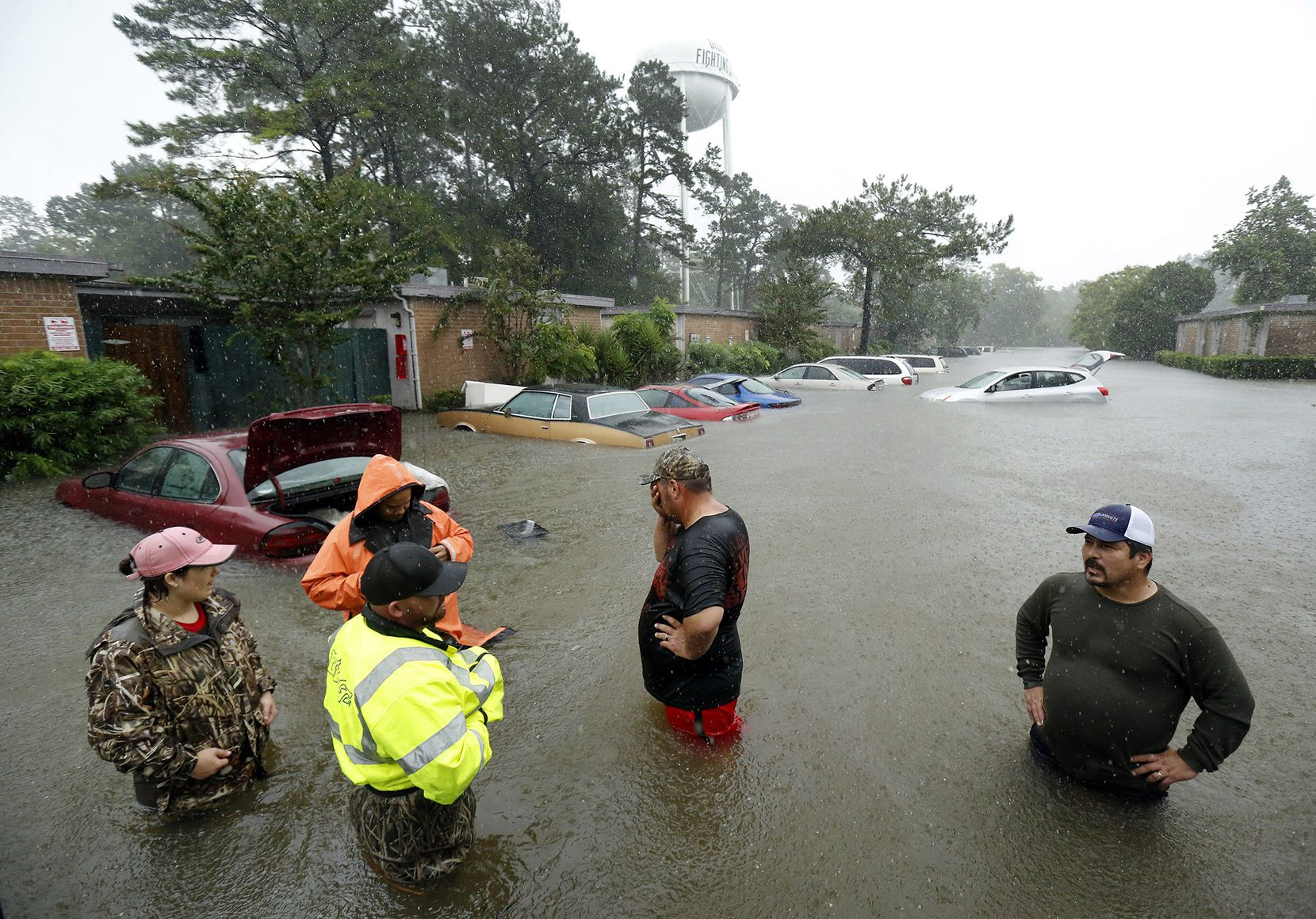 Local volunteers including Christina Crump (left) and her husband Aaron Crump (foreground), and Zach Brandenburg (second from right) stood in waist-high water and a downpour from Tropical Storm Harvey as thy waited for the military-type hauler to start after it became flooded out, Monday, August 28, 2017 in Dickinson, Texas. The crew was helping evacuate distressed residents from their rain-soaked Dickinson homes during welfare checks. Later residents were given a mandatory evacuation notice. Residents were transported to City Hall and the First Baptist Church for transport to the Brown Convention Center in Houston.