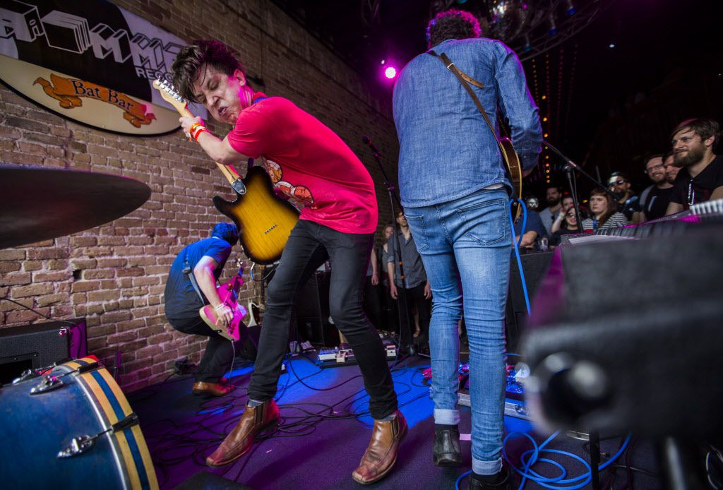 Guitar player and vocalist Billy Yost, left, of Chicago, gets into his performance with his band, The Kickback, at Bat Bar during the SXSW music festival on Thursday in Austin.