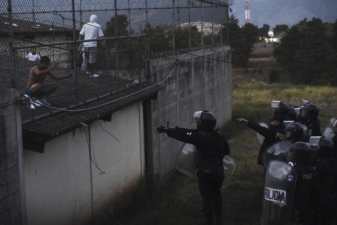Los presos suben al tejado mientras la policía intenta tomar el control durante un motín en el reformatorio para jóvenes y hombres Centro Correccional Etapa II en San José Pinula, Guatemala, el domingo 19 de marzo de 2017. (AP/OLIVER DE ROS)