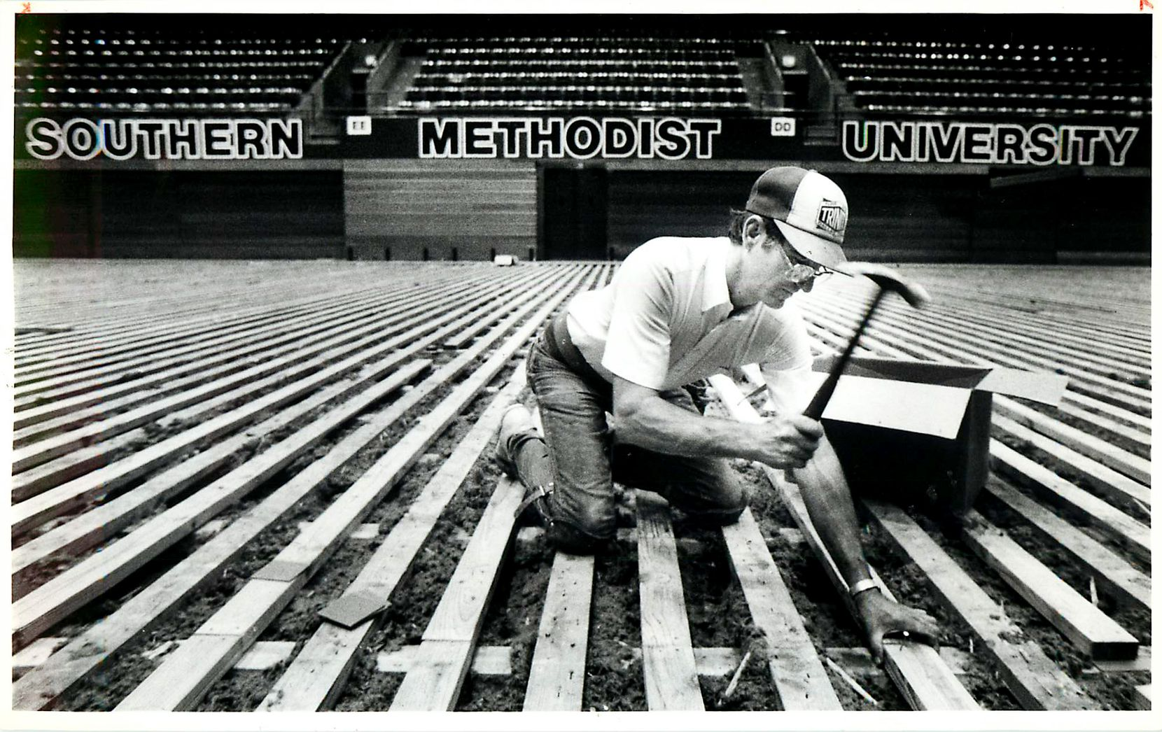 """Original caption (revised to add date and city): """"Wayne Smith, of Trinity Floor, hammers nails into the base of the new floor being installed in Moody Coliseum at SMU in Dallas August 18, 1986. The work was started two weeks ago and will continue for another month and a half."""""""