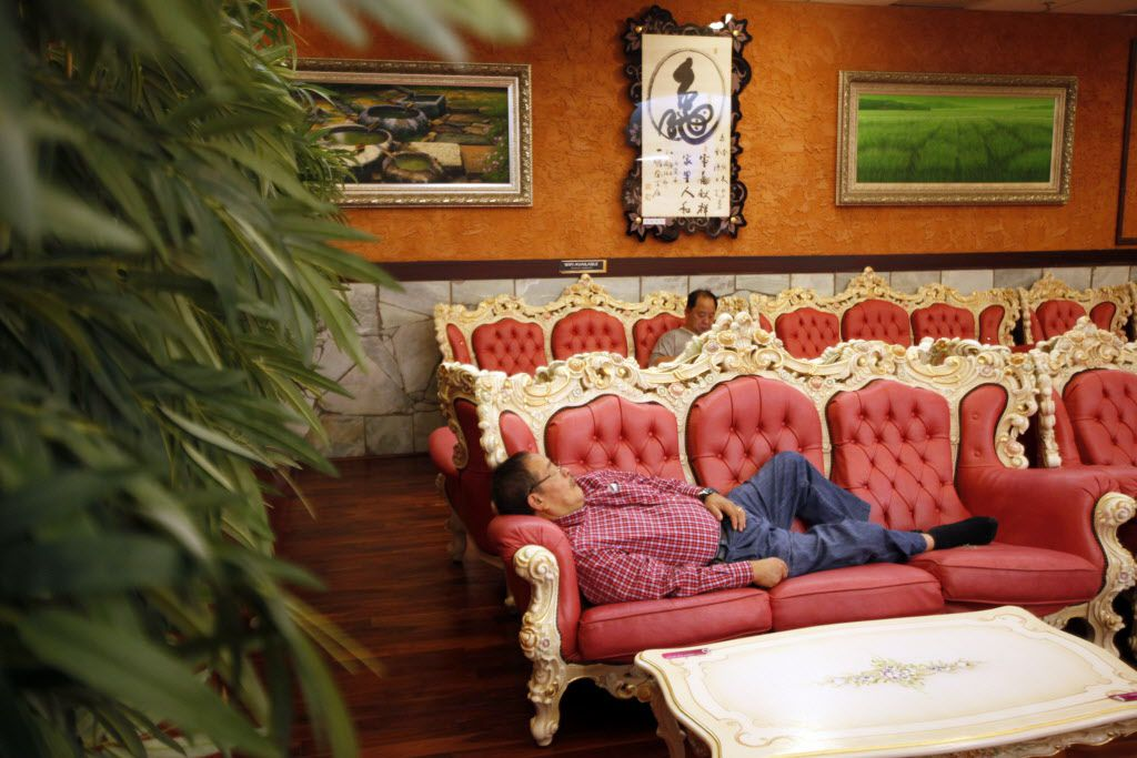 An unidentified man sleeps on couch near the food court inside King Spa, on Wednesday, Oct. 06, 2015 in Dallas.