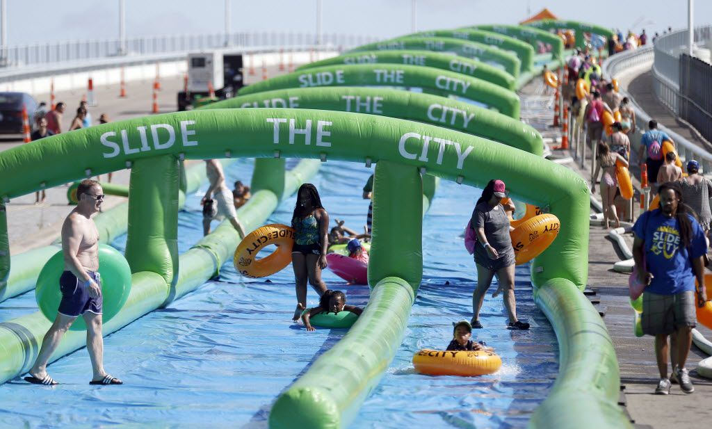 Water sliders slide down a 1,000 foot water slide and walk back to the top during the Slide the City event in the 3400 block of Sylvan Ave. in Dallas, Saturday, June 25, 2016. (Brandon Wade/Special Contributor)Who says