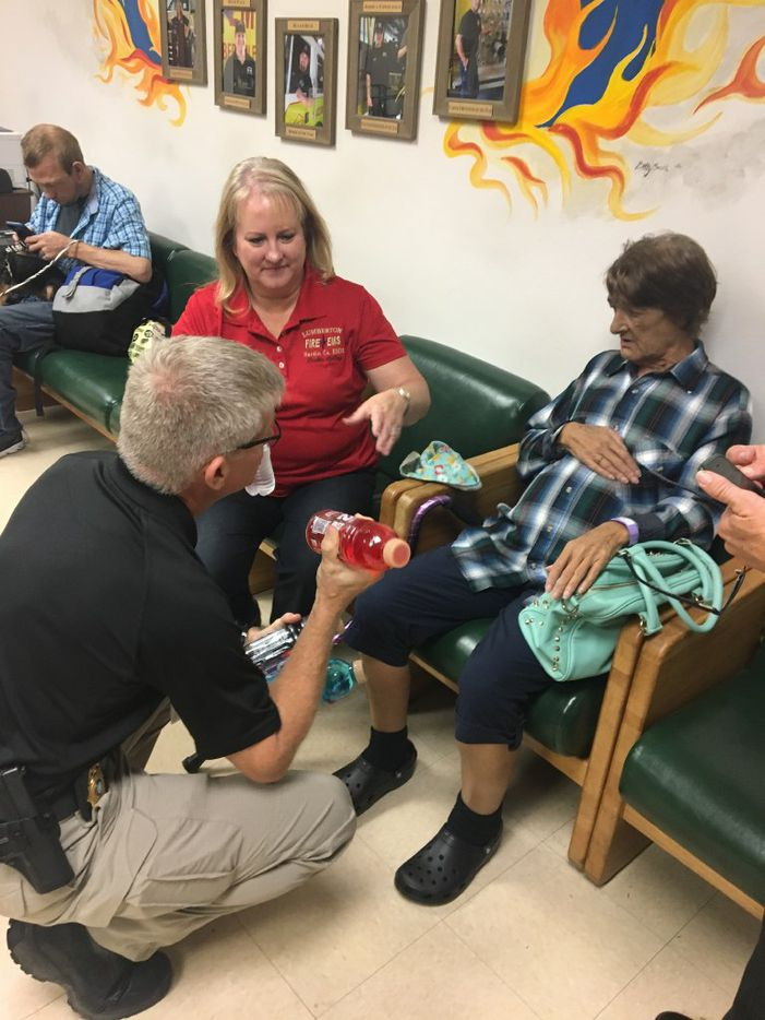 Lumberton Fire Chief Jeff McNeel offers dialysis patient Mary Haynes, 59, right, some gatorade as fire department administrator Beckie Kelley looks on as Haynes awaits a helicopter ride to a hospital on Aug. 31, 2017.