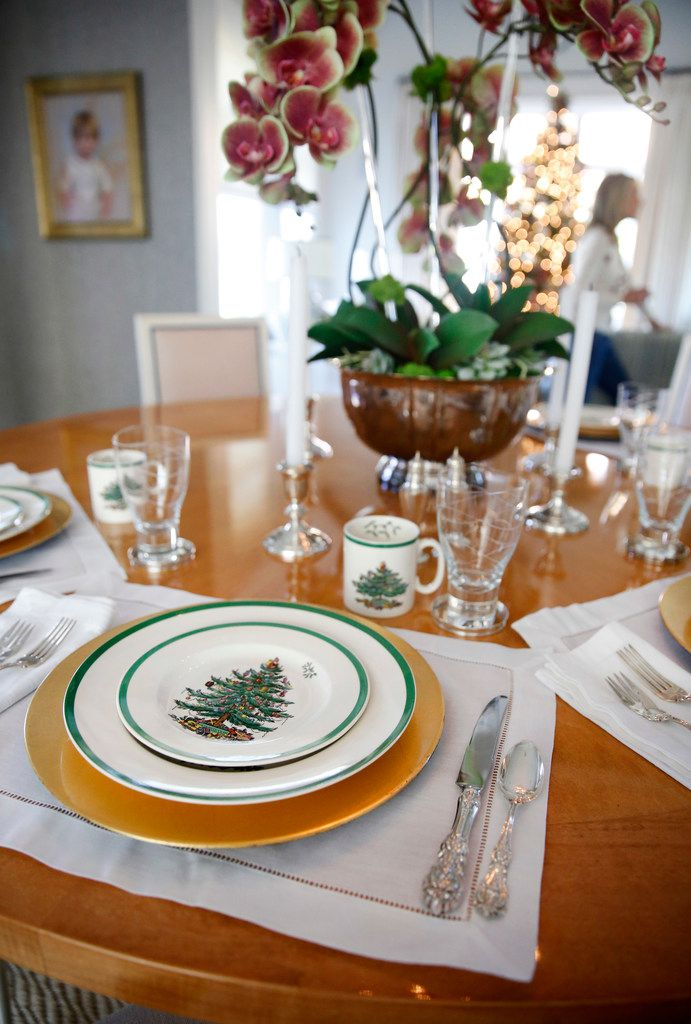 LIke her mother and grandmother before her, Meredith Land, with help from daughter McCall, sets her table in December with Spode's Christmas Tree dishes.