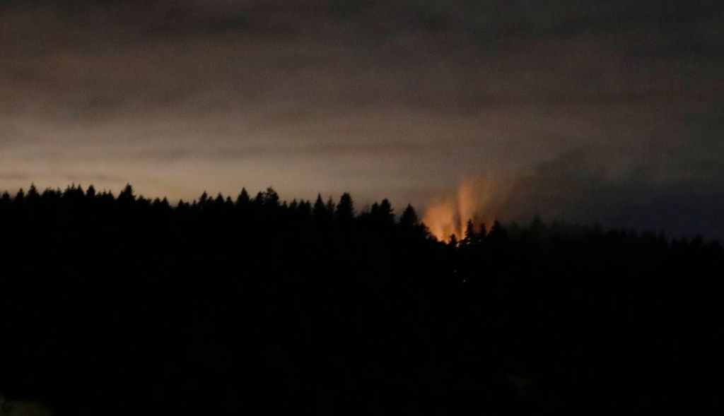 In this long-exposure photo, smoke and an orange glow are seen on Ketron Island in Washington state early Saturday from near Steilacoom, Wash. On Friday, an airline mechanic stole an empty Horizon Air turboprop plane, took off from Seattle-Tacoma International Airport and was chased by military jets before crashing on the small Puget Sound island Friday, officials said.