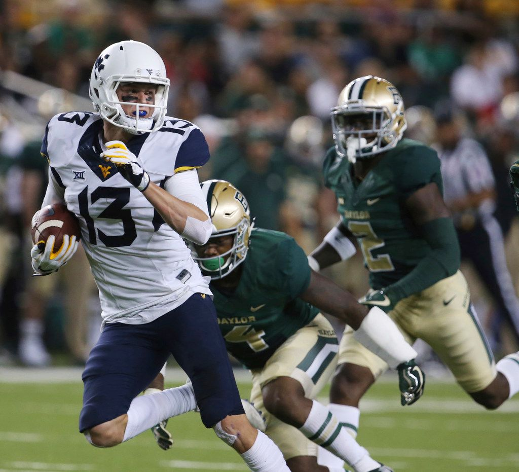 FILE - In this Oct. 21, 2017, file photo, West Virginia wide receiver David Sills V, left, scores past Baylor cornerback Grayland Arnold and safety Taion Sells, right, in the second half of an NCAA college football game in Waco, Texas. West Virginia will play Utah in the Heart of Dallas Bowl Tuesday, Dec. 26. (Rod Aydelotte/Waco Tribune-Herald via AP, File)