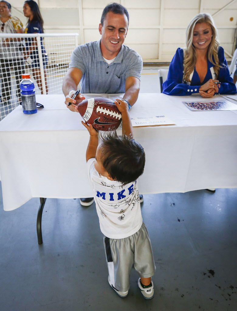 Dallas Cowboys kicker Dan Bailey autographs a football for 18-month-old Mikey Robinson as the team participates in an autograph signing for military personnel and their families after arrival at Naval Base Ventura County at Point Mugu on Tuesday, July 28, 2015,  in Oxnard, CA, prior to the start of their NFL training camp. (Smiley N. Pool/The Dallas Morning News)