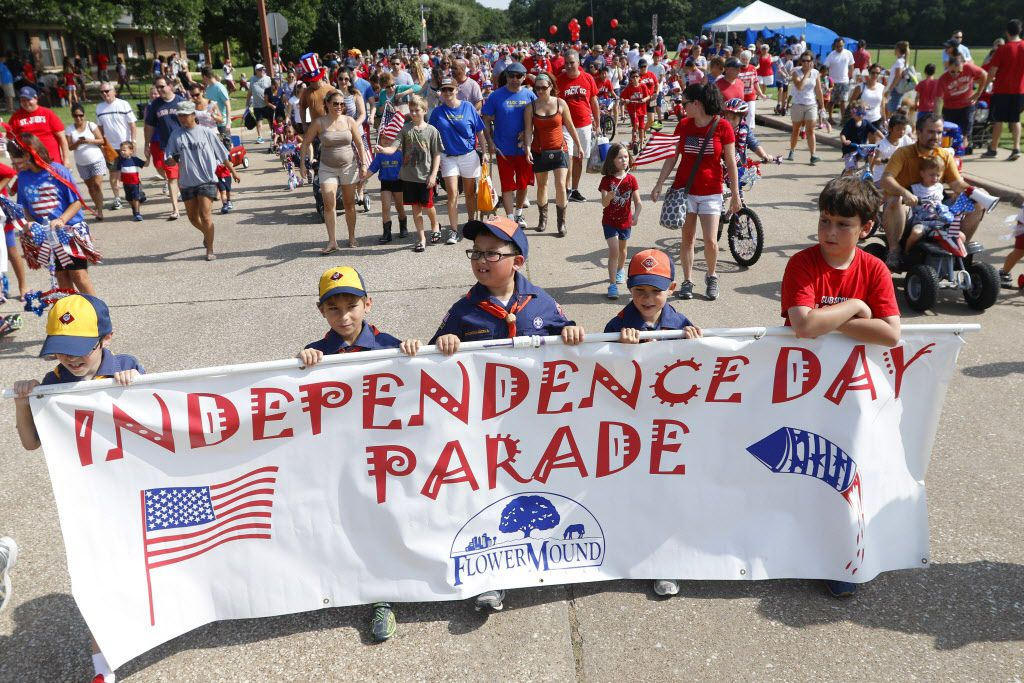 Families march down Timber Creek Rd. during the Independence Fest Children's Parade in Flower Mound, Texas on Saturday, July, 4, 2015.