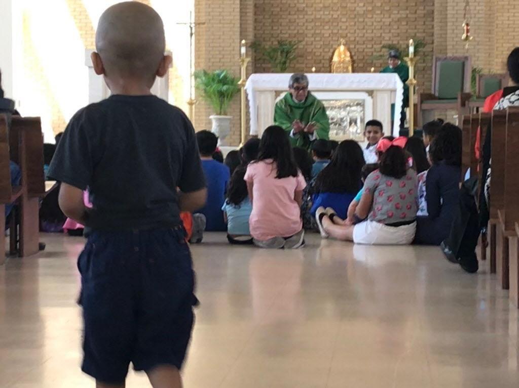 El padre Martin Moreno reza con los hijos de los feligreses de la iglesia católica Santa Cecilia para bendecir su regreso a clases el domingo. JAVIER GIRIBET/AL DÍA
