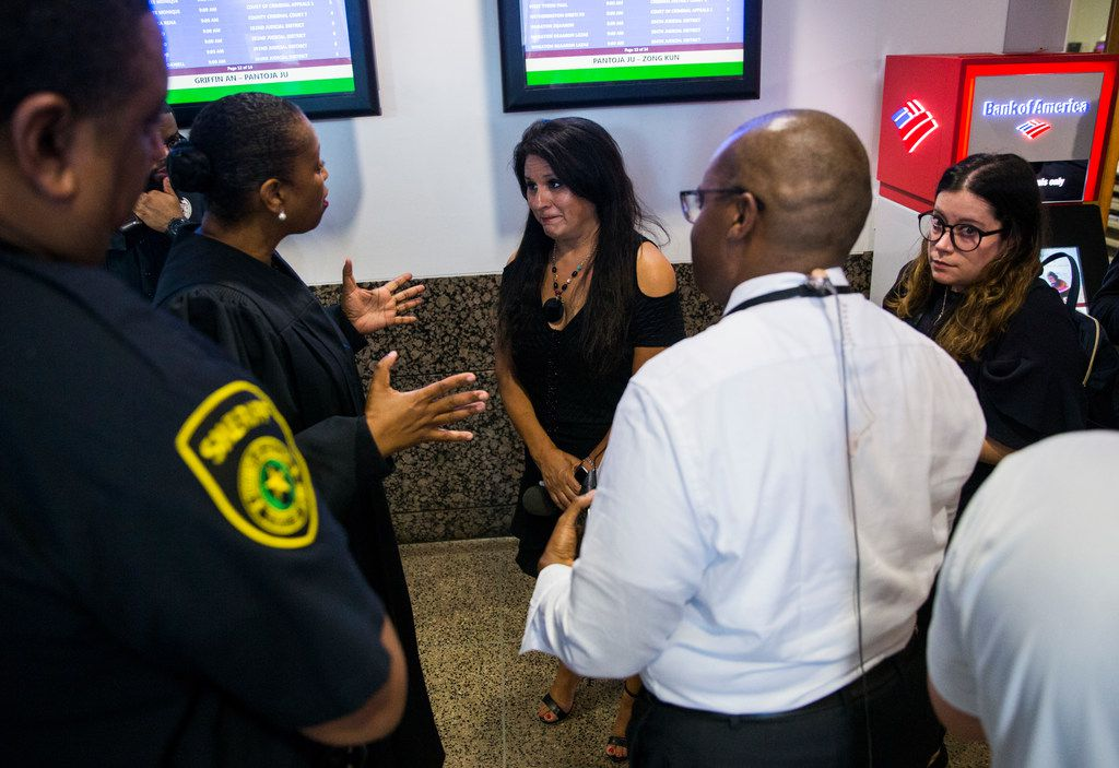 District Judge Tammy Kemp (second from left) talks with reporters in the hallway outside the jury room as potential jurors are selected for the Amber Guyger trial on Friday. The media was briefly barred from the room but later allowed inside once the crowd of potential jurors had thinned.