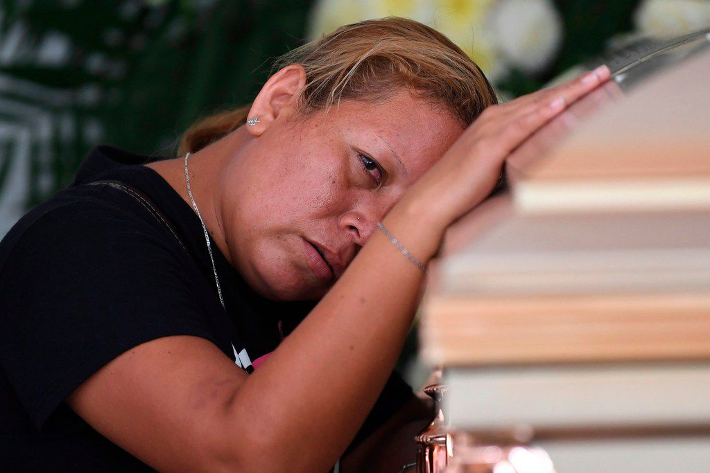 A woman mourns as she leans against the coffin of a victim of the attack at the Caballo Blanco bar (White Horse bar), during a funeral service at a cemetery in Coatzacoalcos, Veracruz State, Mexico, on August 29, 2019. Gunmen burst into the strip club and fired in a hail of bullets killing at least 28 people and badly wounding nine as they trapped revellers inside and started a raging fire on Tuesday night. Many of the dead were dancers who worked there, according to managers.