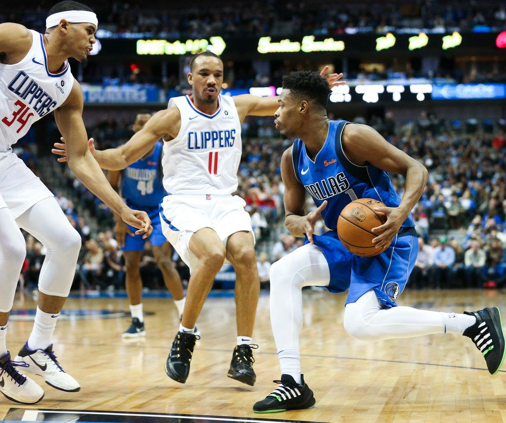 Dallas Mavericks guard Dennis Smith Jr. (1) looks to pass as he is defended by LA Clippers forward Tobias Harris (34) and guard Avery Bradley (11) during an NBA basketball game at American Airline Center in Dallas on Tuesday, Jan. 22, 2019.  (Shaban Athuman/The Dallas Morning News)