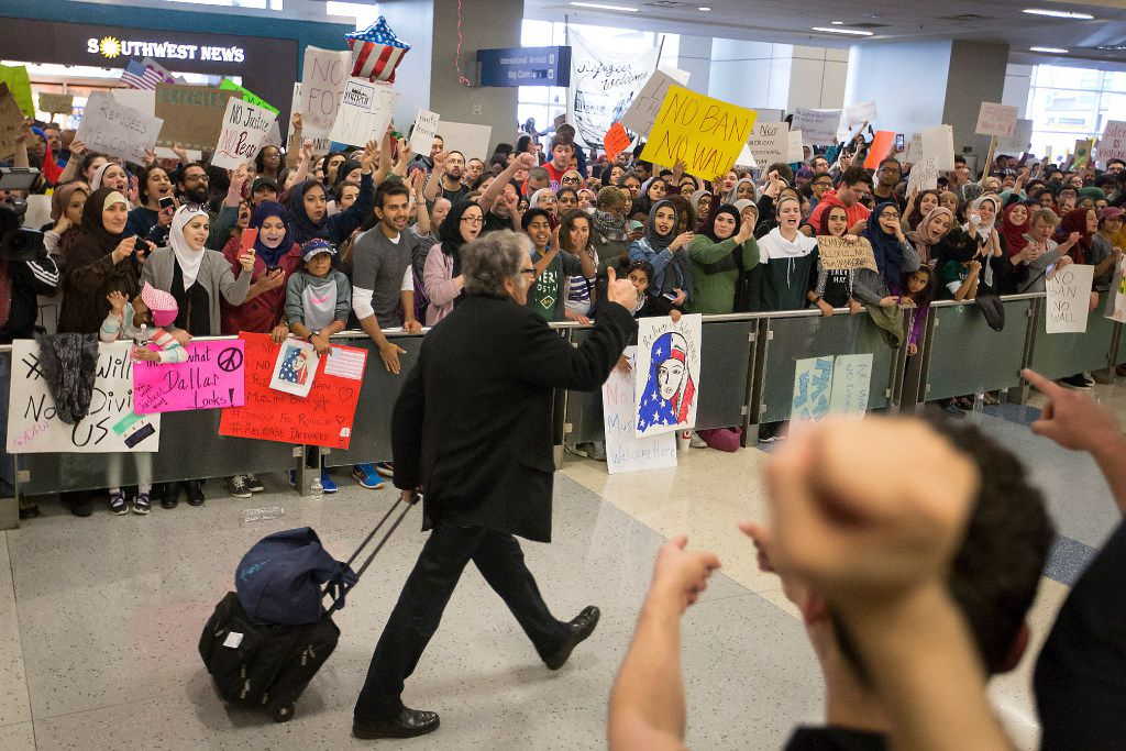 A passenger gives a thumbs up to protestors in the international arrivals hall at DFW International Airport gathered in opposition to President Donald Trump's executive order barring certain travelers on Sunday, Jan. 29, 2017. (Smiley N. Pool/The Dallas Morning News)