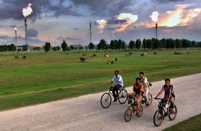 Indonesian men cycle past the enormous Arun natural gas fields in the Aceh, Indonesia.