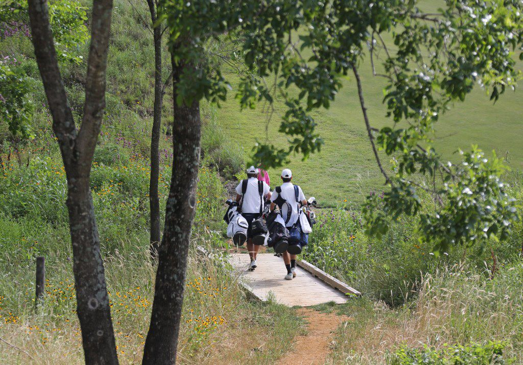 Caddies carry clubs for players along the course during a tour of the Trinity Forest Golf Club in Dallas, photographed on Tuesday, May 16, 2017. (Louis DeLuca/The Dallas Morning News)