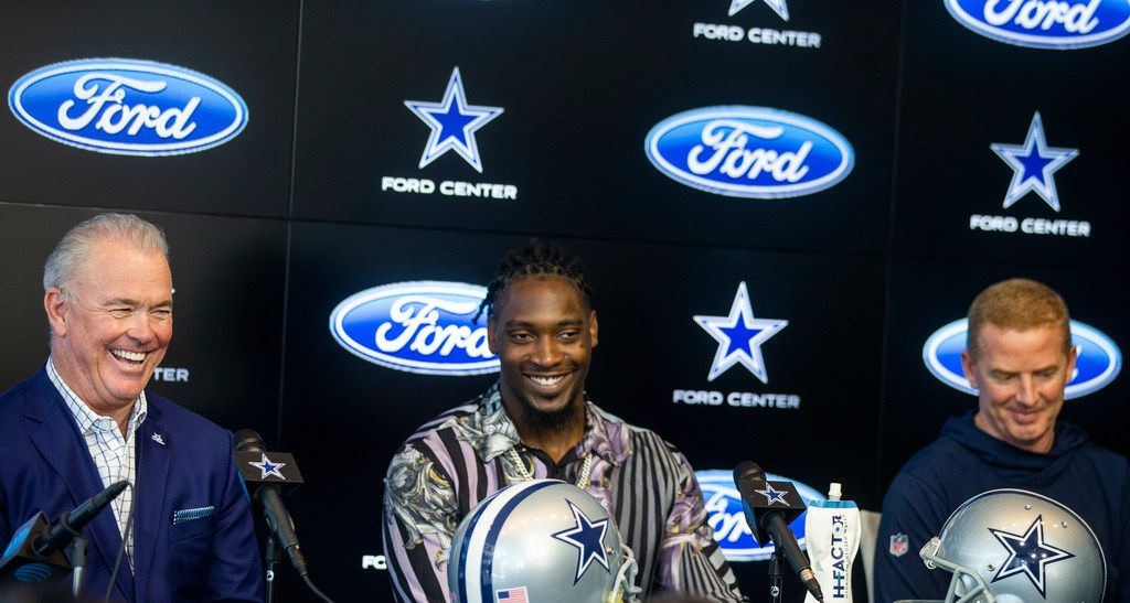 Dallas Cowboys CEO Stephen Jones, left, laughs along with defensive end Demarcus Lawrence and head coach Jason Garrett as owner Jerry Jones gives remarks during a press conference at The Star in Frisco, Texas on Tuesday, April 9, 2019. Lawrence is the highest paid player in the franchise history.  (Shaban Athuman/Staff Photographer)