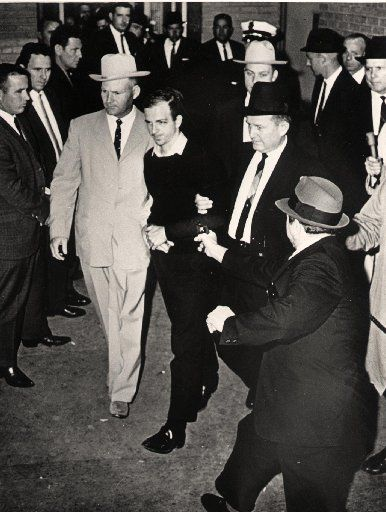Jack Ruby, Dallas nightclub owner, steps out with a gun in hand a moment before Lee Harvey Oswald, charged with the assassination of President Kennedy, was shot in the stomach at the Dallas city jail.