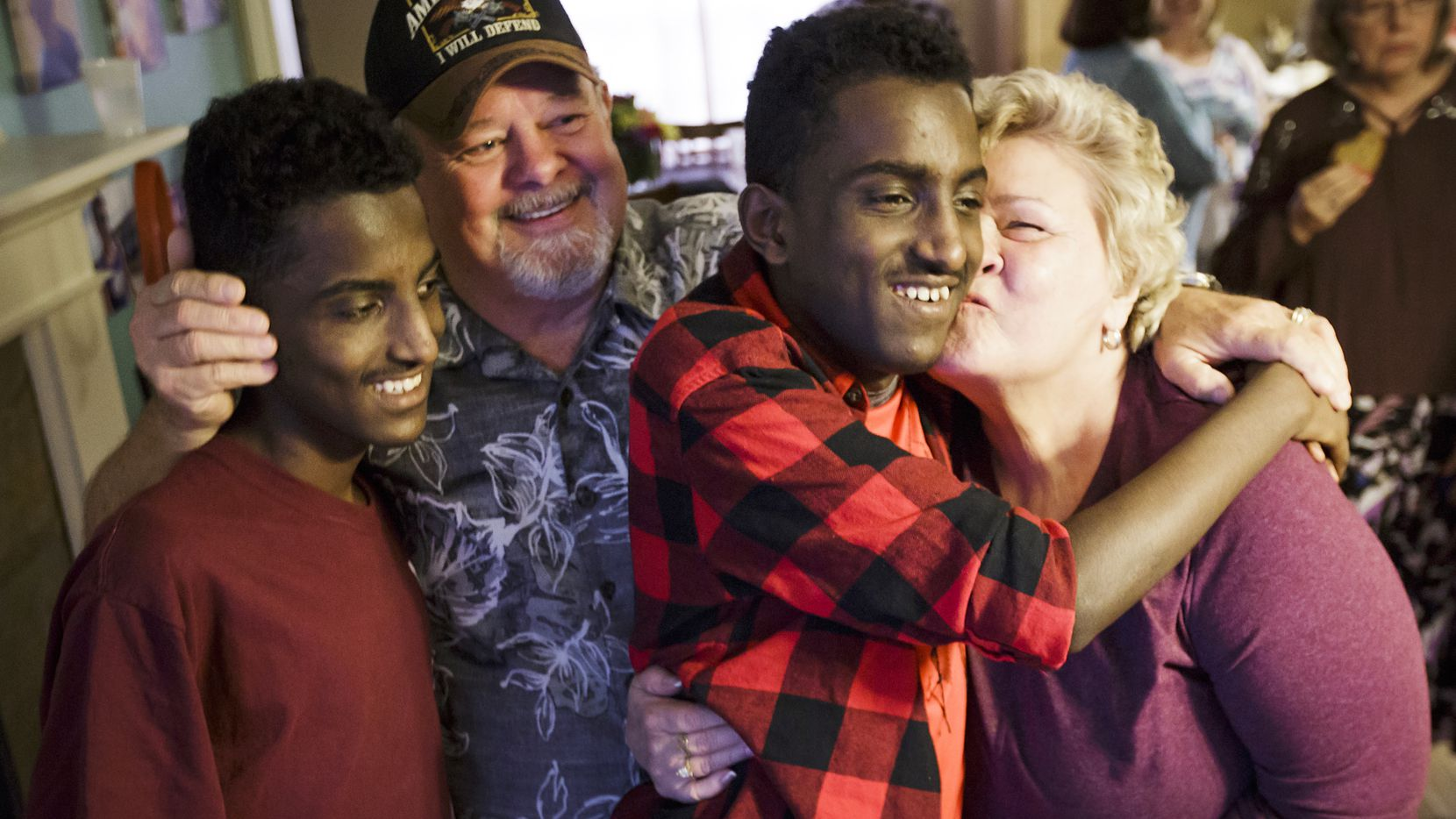 Marcos Bogale (center) gets a kiss from Linda Keylon as his twin Tamirat gets a hug from Gary Keylon  during a going away party for the twins on Monday, April 24, 2017, in Plano. The Ethiopian twins will leave Texas after  traveling to the state in December for surgery to treat their severe scoliosis. The brothers have met FC Dallas players, enrolled in high school and now the community plans to host two fundraisers before they go back home to Addis Ababa, Ehtiopia on Wednesday.  The Keylon's are the parents of the boys' host family. (Smiley N. Pool/The Dallas Morning News)