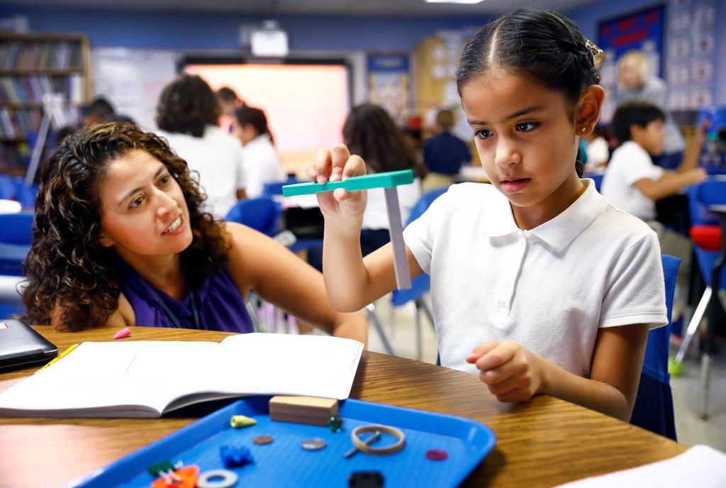 Third-grader Jaime Tobon looks at the power of a magnet as her dual language science teacher Carmen Arellano questions her about what makes it happen at Arthur Kramer Elementary in North Dallas last fall.