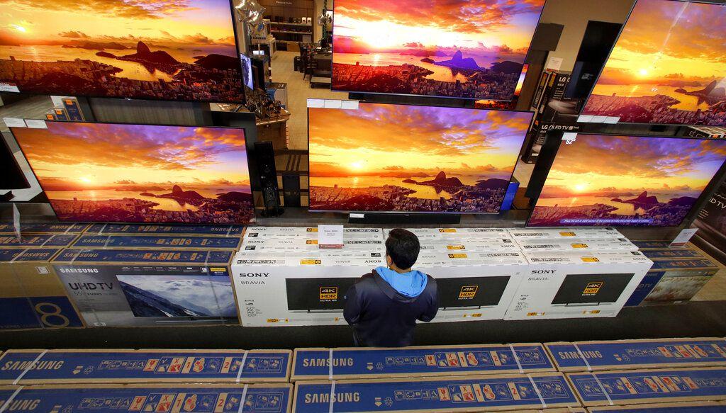 ARCHIVO – En esta fotografía del 22 de noviembre de 2018 un hombre observa televisiones en una tienda de Best Buy en Overland Park, Kansas. (AP Foto/Charlie Riedel, Archivo)